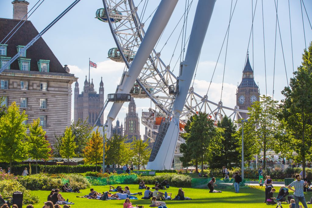 People sat in the park on a sunny day next to the feet of The London Eye. Big Ben and Westminster are in the background.