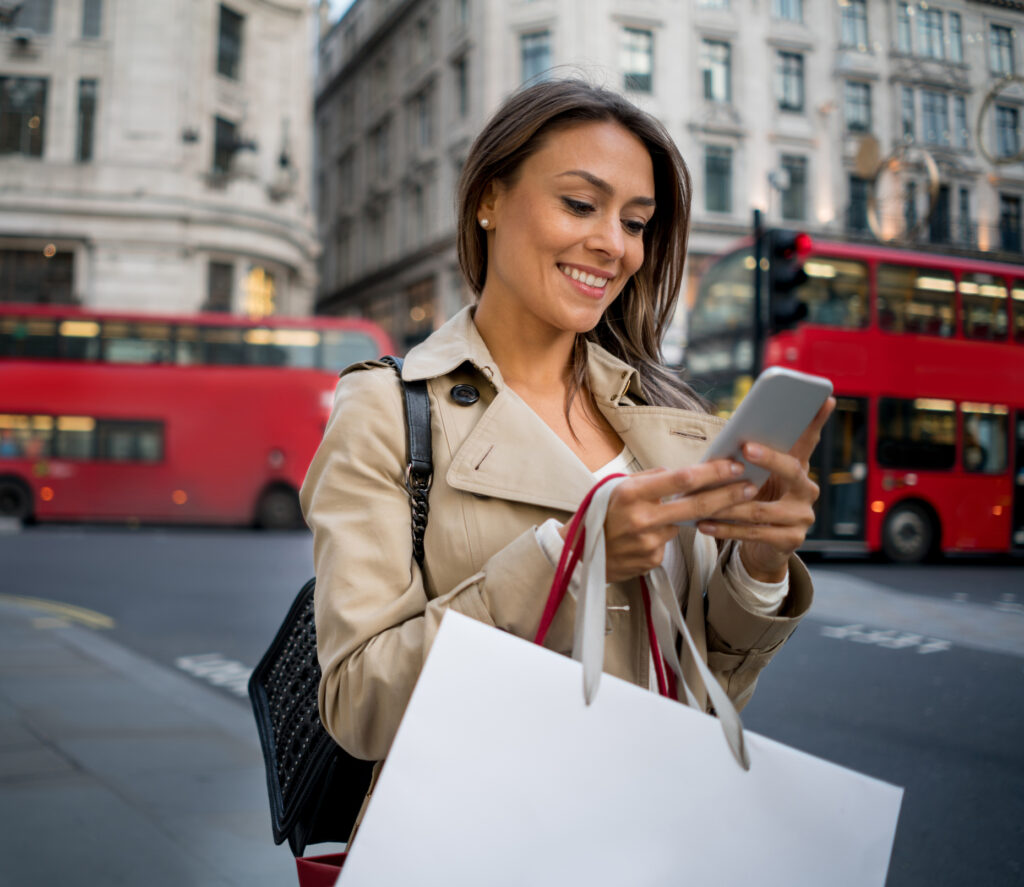 Woman Christmas shopping in London and texting on her cell phone looking happy