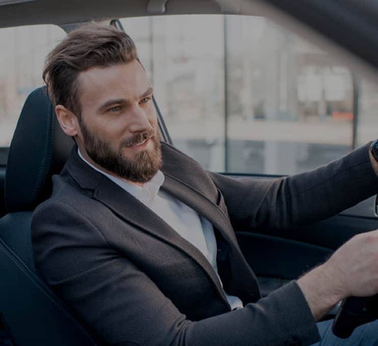 man in suit driving taxi